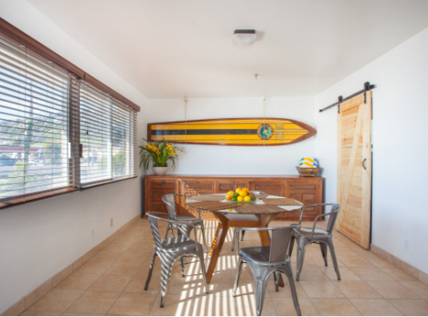 Dining area with surfboard hanging on the wall